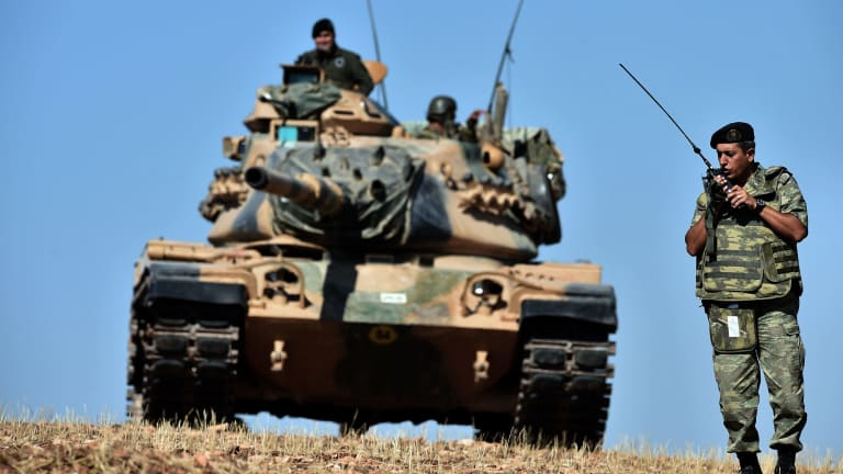 INACTION: Turkish tanks line up on a hill outside the village of Mursitpinar next to the Syrian town of Kobane.
