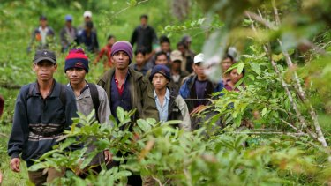 Montagnard hill tribesmen walk towards the main road after emerging from dense forest 70km north-east of Ban Lung, Cambodia in 2004.