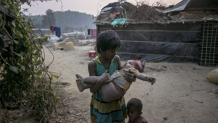 A girl carries a toddler in her arms in Kutapalong Rohingya refugee camp in Cox's Bazar, Bangladesh.