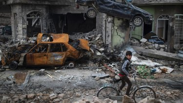 A boy rides his bike past destroyed cars and houses in a neighbourhood recently liberated by Iraqi security forces, on the western side of Mosul, on March 19.