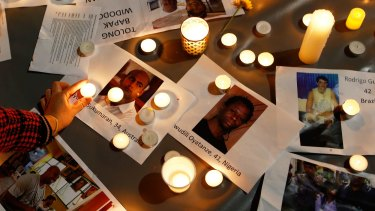 A woman places a candle on top of pictures of the executed prisoners at a vigil in Sydney.