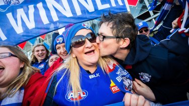 Moore gets a kiss from fellow Bulldogs supporter Chris Patmore at Whitten Oval.