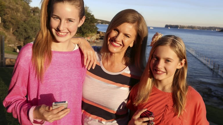 The world's longest umbilical cord?: Emma (left) and Imogen Murray hold their mobile phones, which their mother Trish gave them when they were in years 5 and 4 respectively.