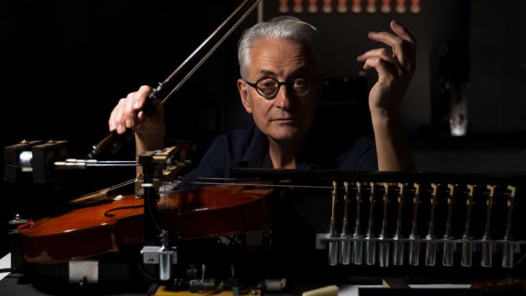 """Jon Rose with his violin robot, which plays """"the sound of money""""."""