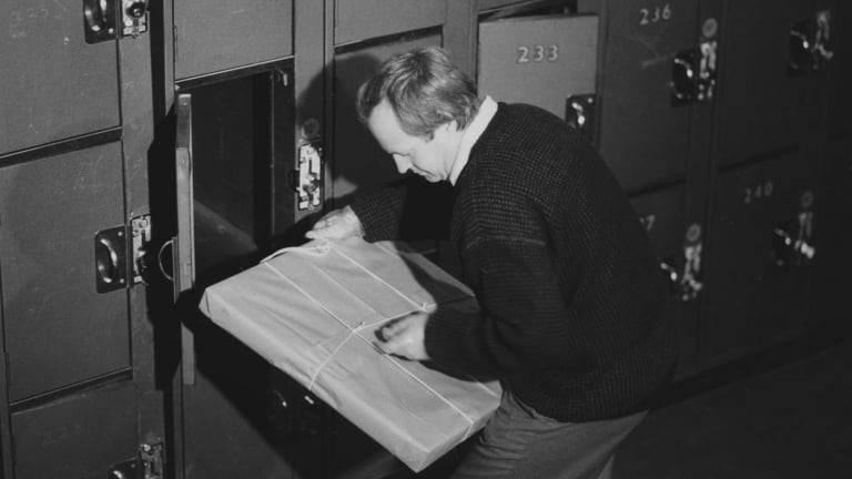 Victoria Police forensic scientist Neil Holland removes the package containing the painting from locker 227 Spencer Street Station on August 20, 1986.
