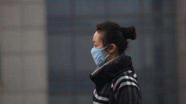 A woman wears a mask as she walks on a street in Beijing.