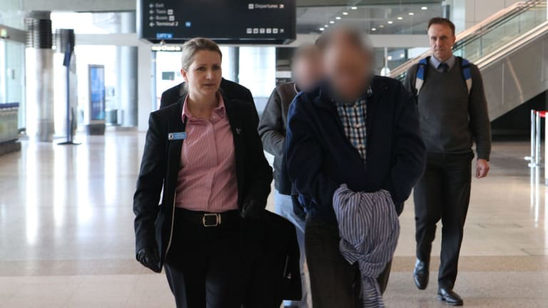 The two suspects, with their faces obscured here, arrive at Sydney Airport, escorted by police.