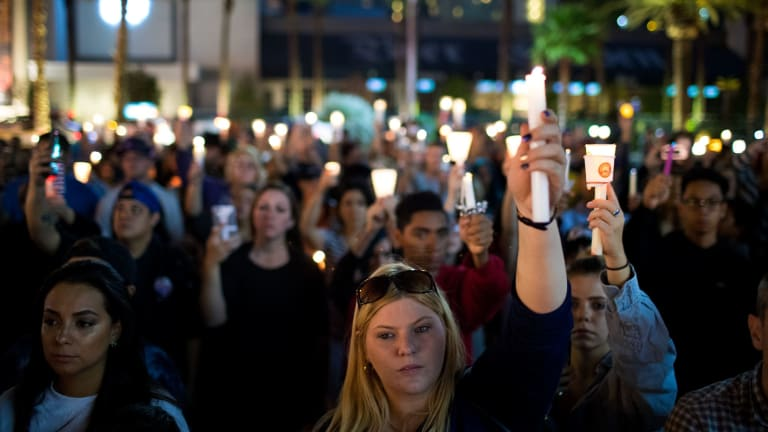 Mourners hold a vigil in Las Vegas after 58 people were killed.