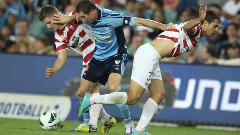 Strong feelings: Brett Emerton holds off two defenders in a 2012 Sydney derby.