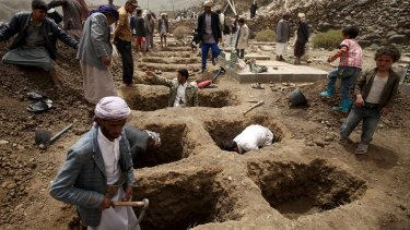 People dig graves for the victims of an air strike in Okash village near Sanaa on April 4.