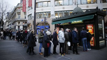 """People queue to get a copy of satirical French magazine <i>Charlie Hebdo</i>, titled """"Tout est pardonne"""" (""""All is forgiven"""") and showing a caricature of Prophet Mohammad, in front of a kiosk in Paris."""