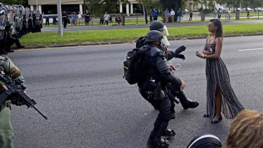 This photograph, by Max Becherer, shows a different angle of the woman moments before she is arrested.