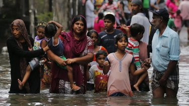 Sri Lankans wade through a road submerged in flood waters in Colombo.