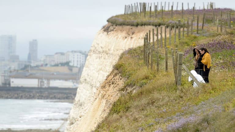 People lay flowers at the clifftop where Arthur Cave fell to his death.