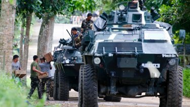 Troops load ammunition and supplies as a convoy of APCs head to the site three days after Muslim militants lay siege in Marawi city.