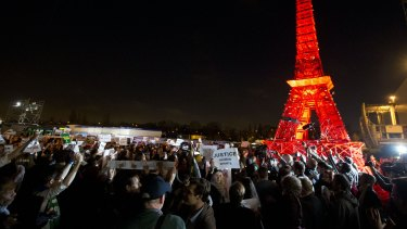 Activists gather next to a mini Eiffel Tower after a sit-in protest to denounce a draft text released at the climate conference.