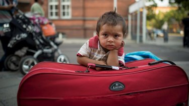 A migrant boy waits at his parents' suitcase as they leave the Berlin State Office for Health and Social Affairs with other newly arrived refugees on Monday.