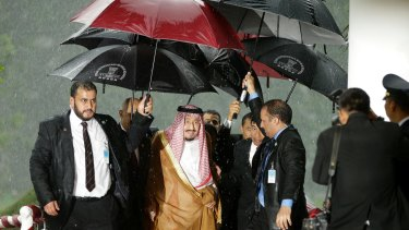 Saudi King Salman walks under the umbrellas during a heavy rain at the presidential palace in Indonesia.