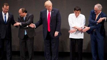 "From left, Russian Prime Minister Dmitry Medvedev, Vietnamese President Tran Dai Quang, U.S. President Donald Trump, Philippine President Rodrigo Duterte and Australian Prime Minister Malcolm Turnbull, prepare to do the ""ASEAN-way handshake""."