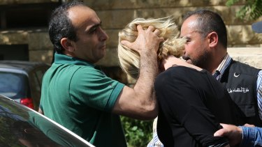A Lebanese plainclothes policeman prevents Tara Brown from looking towards journalists as she was taken from the courthouse while under arrest in Lebanon.