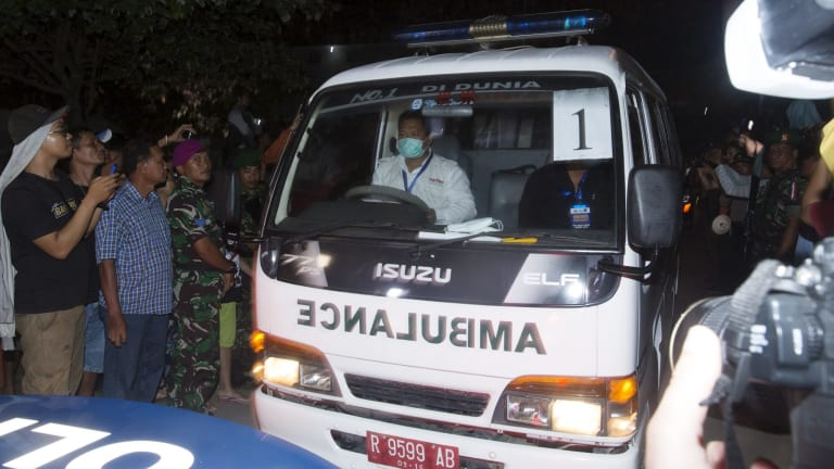 An ambulance leaves Cilacap carrying a coffin.