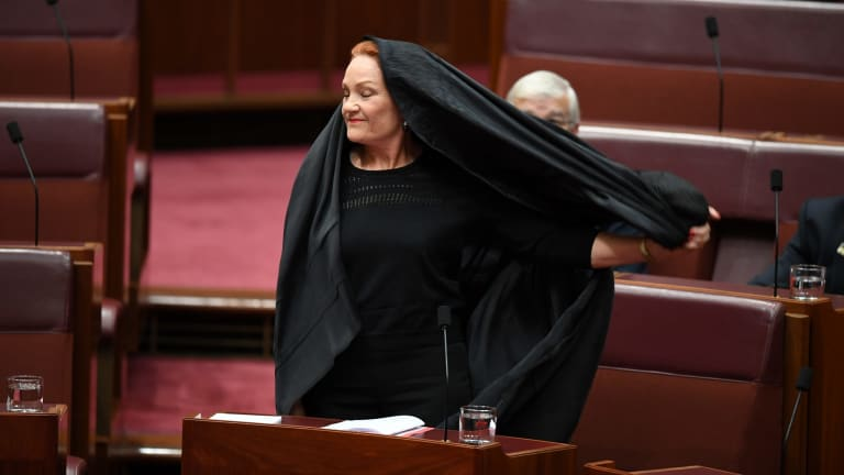 One Nation senator Pauline Hanson takes off the burqa. The stunt would likely not have been allowed under old Senate rules.