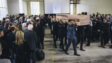 Pallbearers carry the bespoke coffin of designer Robert Foster at his funeral at the Fitters Workshop.