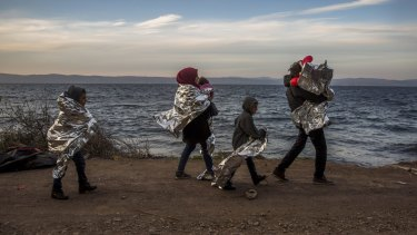 A Syrian family covered with thermal blankets walk after they arrived from Turkey at the Greek island of Lesbos in October.
