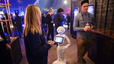 Pepper the humanoid robot interacts with an attendee at Slush 2016.