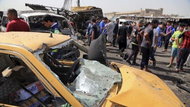 Citizens inspect the scene of a suicide car bomb which hit a crowded outdoor market in Baghdad's eastern Shiite neighborhood of Sadr City on Tuesday.
