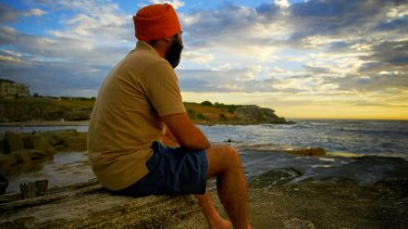 Tourist Parminder Singh from India watches the sun rise at Clovelly Beach on Tuesday morning.