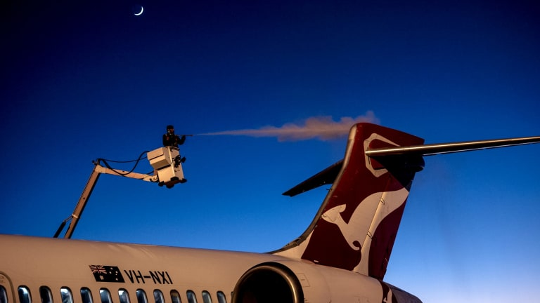An engineer removes ice from a Qantas aircraft at Canberra airport in sub-zero temperatures.