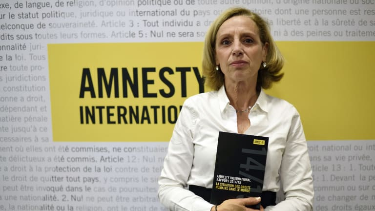 Amnesty International France President Genevieve Garrigos holds a copy of the 415-page annual report, which details abuses in 160 countries.