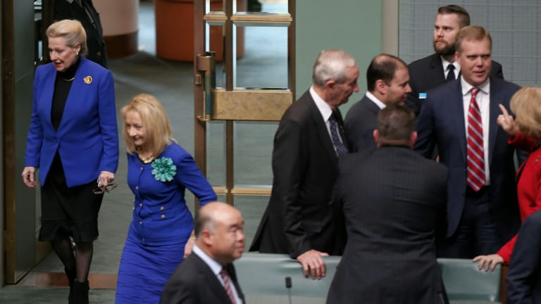 Former speaker Bronwyn Bishop enters the chamber while Tony Smith is congratulated by colleagues in the House of Representatives following his selection as her replacement.