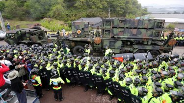 South Korean police protect a US military vehicle from protesters who oppose a plan to deploy the THAAD system against North Korean attack.