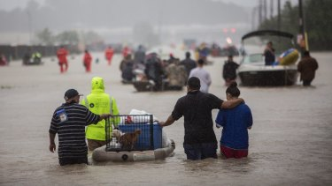 First responders and volunteer rescuers help evacuate people stranded by floodwaters on the outskirts of Houston.