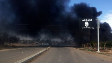Smoke billows behind an Islamic State street sign during clashes between the terrorist group and Iraqi security forces in Sadiyah, north of Baghdad, in 2014.