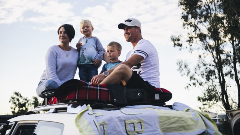Dustrin and Kirstie Stephen with sons Jarrod, 5, and Tyler, 3, perch on top of their four-wheel drive to get a better view at Mount Ainslie.