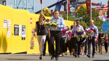 Dreamworld chief executive Craig Davidson and his employees leave flowers at the site on Wednesday.
