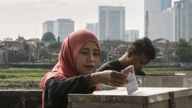A woman casts her ballot in the election for Jakarta's governor on Wednesday.