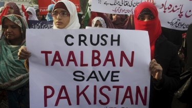 Protesters condemn the Taliban attack on a military-run school in Peshawar.