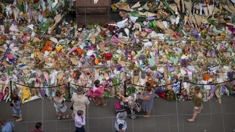 People lay flowers at the memorial to the victims in the wake of the Bourke Street attack.