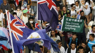 Protesters carry Hong Kong colonial flags and anti-China placards during a march in Hong Kong on July 1, 2015, the day marking the 18th anniversary of Hong Kong's handover from Britain to Chinese sovereignty.