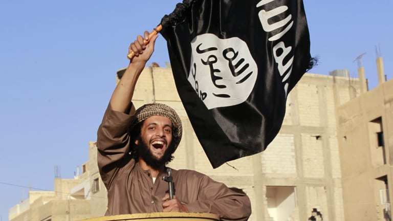 Accentuating the positive: a man waves an IS flag in streets of Syria's north-eastern Raqqa province.