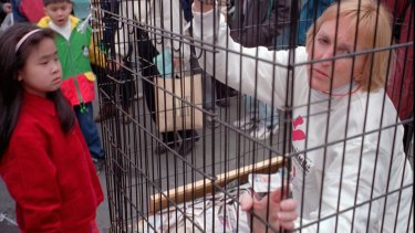 Ingrid Newkirk, president of People for the Ethical Treatment of Animals, sits in a cage at the sprawling Shihlin traditional night market in Taipei in 1998, in protest against the treatment of dogs, which are sold at the market.