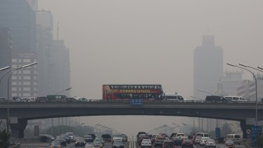Pollution haze shrouds heavy traffic on the roads of Beijing on Tuesday. The Chinese capital city was hit by thick pollution although municipal transport authorities set up three car-free zones for World Car Free Day.