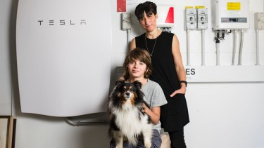 Sophie Jensen with her son Huxley 12, and dog Ghillie, in front of their Tesla battery.