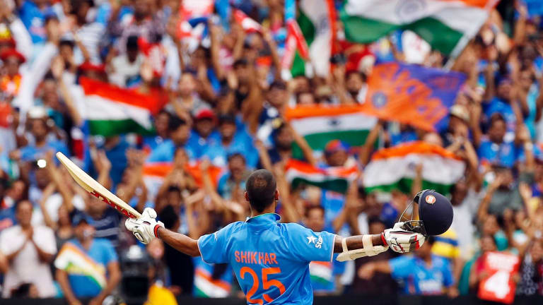 India's Shikhar Dhawan acknowledges supporters in the crowd as he celebrates after reaching a century during a Cricket World Cup match at the Melbourne Cricket Ground.