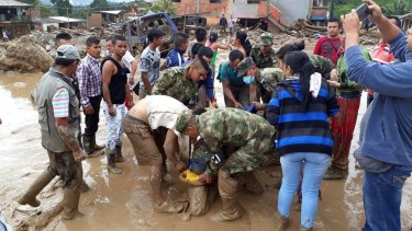Locals work alongside soldiers to rescue the injured.