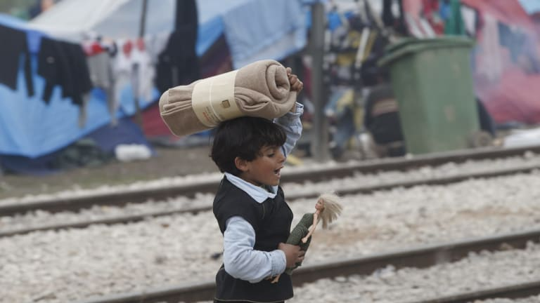 A child of a migrant family walks holding a doll in the makeshift refugee camp at the northern Greek border point of Idomeni, Greece, on Thursday.